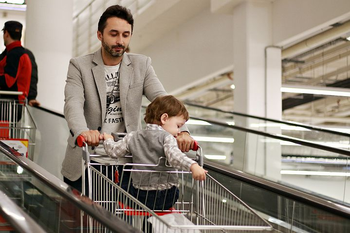 man going to the grocery with his kid sitting in the push cart